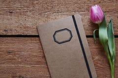 一个减速火箭的笔记本和郁金香春天大气在木书桌上 免版税库存照片