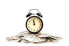 一个减速火箭的闹钟建议的随着时间的推移储款概念站立在一堆金钱顶部 图库摄影