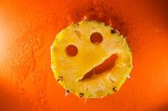 一个切片在橙色背景,水平的射击的菠萝 免版税图库摄影