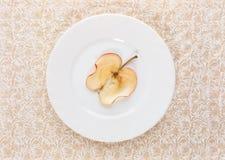 一个切片在白色板材的干苹果在米黄华丽被仿造的背景 图库摄影