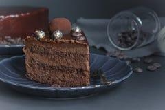 一个切片巧克力果仁巧克力蛋糕,与坚果的点心在黑暗的背景 免版税库存图片
