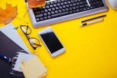 一个创造性的办工室职员的工作区 与一杯咖啡一起使用,使用电话和片剂 免版税库存图片