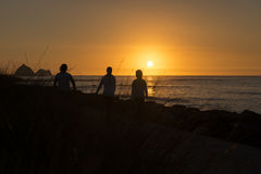 一个剪影的人们反对日落在背景中点燃与太阳在天际 库存照片