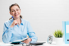 一个办公室工作者的画象在一个白色砖墙上的一张桌上 库存图片