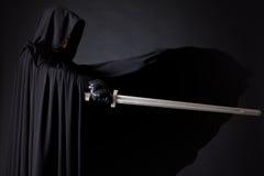 一个勇敢的战士流浪汉的画象一把黑斗篷和剑的在手中 免版税图库摄影