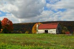 一个北部纽约山坡的美丽的老被风化的谷仓在秋天 库存图片