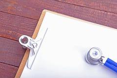 一个医疗听诊器的特写镜头有文件夹的在木backgroun 免版税库存图片