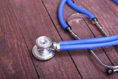 一个医疗听诊器的特写镜头,隔绝在木背景 免版税库存照片