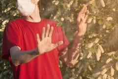 一个医疗面具的一个人显示中止姿态对树花,变态反应原 库存图片