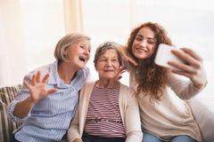 一个十几岁的女孩、母亲和祖母有智能手机的在家 库存图片