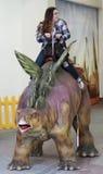 一个十几岁的女孩乘坐剑龙在T雷克斯行星 免版税库存图片