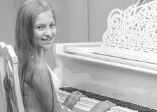 一个十几岁的女孩在一架白色大平台钢琴使用 免版税库存图片