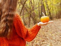 一个十几岁的女孩在她的手上的拿着一个南瓜走在森林里 库存图片
