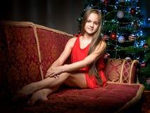 一个十几岁的女孩在新年树附近坐 免版税图库摄影