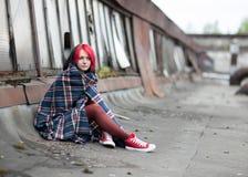 一个十几岁的女孩坐用地毯盖的屋顶 库存照片