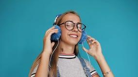 一个十几岁的女孩的画象有长的头发的在投入在耳机,听到音乐和跳舞在的玻璃 股票视频