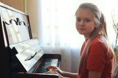 一个十几岁的女孩的14年的画象年纪在家弹钢琴 免版税库存图片