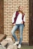一个十几岁的女孩的画象砖墙的背景的 免版税库存图片
