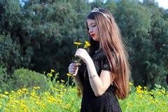 一个十几岁的女孩获得乐趣在菊花的领域 库存图片