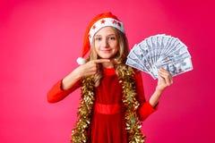 一个十几岁的女孩,戴一个圣诞老人帽子和有在她的脖子的闪亮金属片的, 库存图片