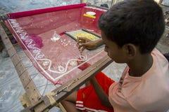 一个十几岁的男孩增加细节到传统Jamdani莎丽服在Mirpur Benarashi Palli,达卡,孟加拉国 图库摄影