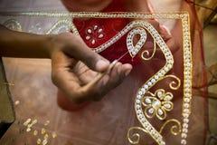 一个十几岁的男孩增加细节到传统Jamdani莎丽服在Mirpur Benarashi Palli,达卡,孟加拉国 免版税图库摄影