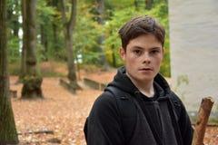 一个十几岁的男孩的画象在秋天森林里 免版税库存照片