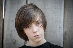 一个十几岁的男孩的画象在木背景前面的 库存图片