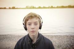 一个十几岁的男孩的画象有耳机的 库存图片