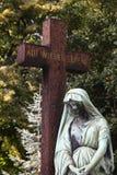 一个十字架和一个天使在公墓 免版税库存照片