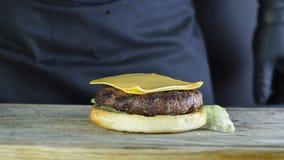 一个半小圆面包的特写镜头一个汉堡的与顶部厨师计划两个切片莴苣和炸肉排的叶子在 股票录像