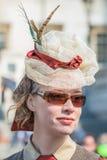 一个华美的羽毛帽子和太阳镜的美丽的少妇 免版税库存照片