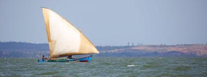 一个单桅三角帆船航行的大图象在沿海水域的 库存图片