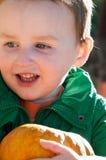 年轻一个南瓜用南瓜在背景中调遣的小孩男孩外部藏品 免版税库存图片