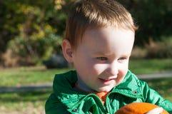 年轻一个南瓜用南瓜在背景中调遣的小孩男孩外部藏品 免版税库存照片