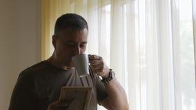 一个卡其色的T恤杉身分的单独人在拿着在一个木制框架的窗口一张照片 人检查照片和 股票录像