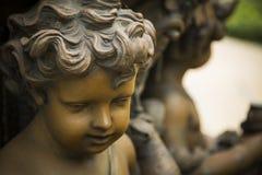 一个卷发的孩子的面孔的古铜色雕象 库存照片