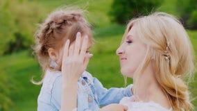 一个卷曲白肤金发的女孩的画象和她的母亲、柔软、关心和母爱 股票录像