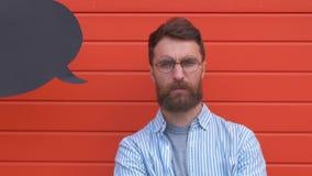 一个压抑年轻人身分和拿着一张黑纸的画象在他的头上的讲话泡影,在红色 影视素材