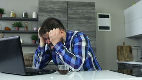 一个厚实的人在膝上型计算机前面的厨房并且开始变得恼怒,掴桌用他的手 一个肥胖人 股票录像