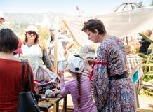 一个参加者在骑士节日在戈伦公园显示访客如何编织与色的螺纹在以色列 免版税图库摄影
