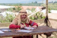 一个参加者在骑士节日坐在桌上并且绘在色纸的一张图画与色的铅笔在戈伦公园 图库摄影