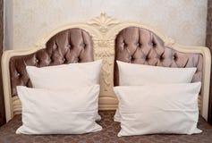 一个双人床的被雕刻的床头板与枕头的 免版税库存照片