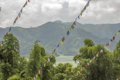一个反对湖和山的绿色森林的多彩多姿的佛教西藏祷告旗子 库存图片