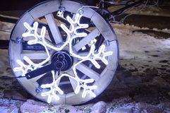一个发光的轮子,以雪花的形式圣诞节诗歌选在推车的一个木轮子 免版税库存图片