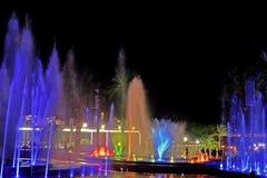 一个发光的音乐喷泉在晚上 飞溅色的水 库存图片