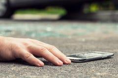 一个受害者和智能手机的手特写镜头在危险inci以后 库存图片