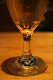 一个变冷的啤酒杯的特写镜头与结露的在木桌上,与选择聚焦 免版税库存照片