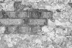 一个古老大厦的老墙壁的灰色纹理与一块被破坏的膏药层数和破裂的砖的 库存照片