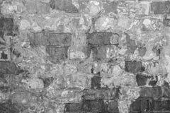 一个古老大厦的老墙壁的灰色纹理与一块被破坏的膏药层数和破裂的砖的 免版税库存照片